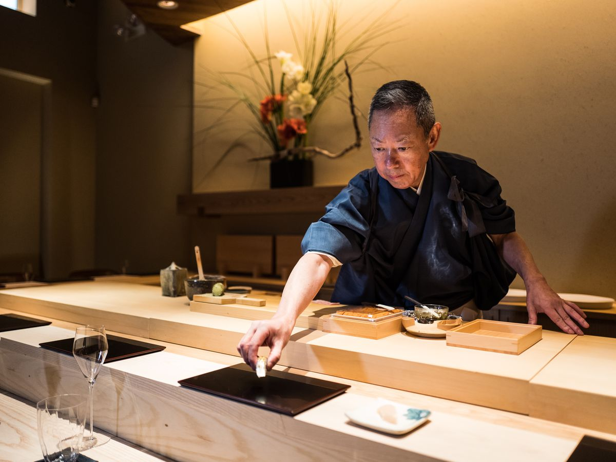 A man in blue clothing stands behind a sushi counter, presenting a piece of sushi to a customer at a placemat set for service