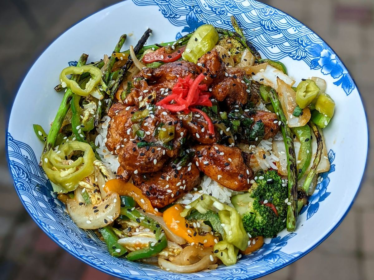 A  blue and white bowl of fried Koji chicken and veggies