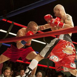 """Chris """"KidKayo"""" Fernandez, right, and Allen Litzau trade blows during their boxing match at the South Towne Expo Center. Fernandez won the bout after four rounds, Saturday, Dec. 15, 2012."""
