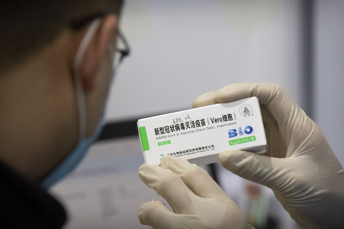 A medical worker shows the box for a coronavirus vaccine to a patient at a vaccination facility in Beijing, Friday, Jan. 15, 2021.