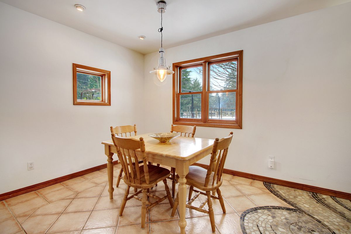A dining room with a wave motif on the floor. A small wooden table with four chairs around it in center of photo. Two windows look to the outside.