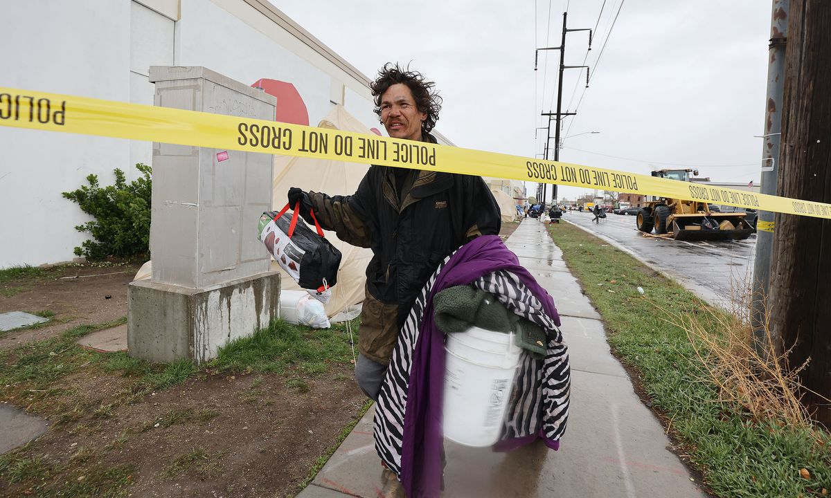 A homeless person wishing to remain anonymous carries his possessions on 800 South as Salt Lake City police enforce a cleanup of homeless camps in Salt Lake City on Wednesday, April 14, 2021.