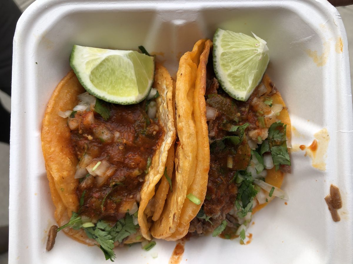 Two meat-filled corn tacos sitting side by side in a white styrofoam container