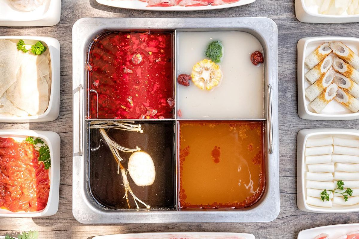 Overhead view of table at HaiDiLao with four-chambered hot pot and various dishes of meat, seafood, and vegetables