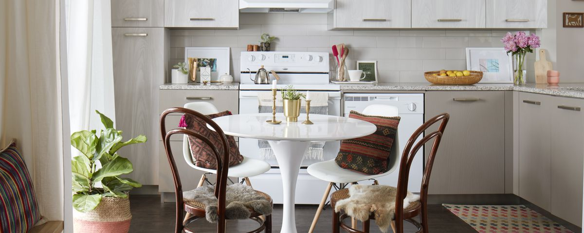 An open-plan kitchen, with a round table at center, around which two dark wood chairs and two white chairs gather. A short green plant sits on the floor to the left of the scene, while small gold objects sit clustered atop the table.