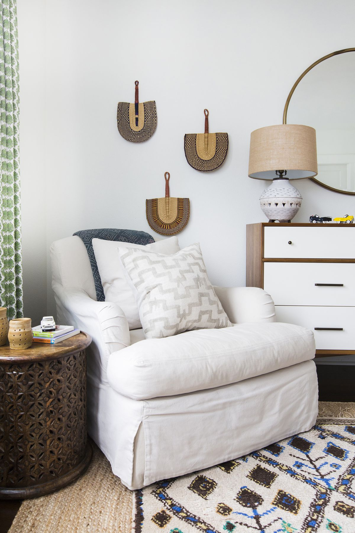 African fans hang on the wall, and a carved African wood table sits beside a white chair.