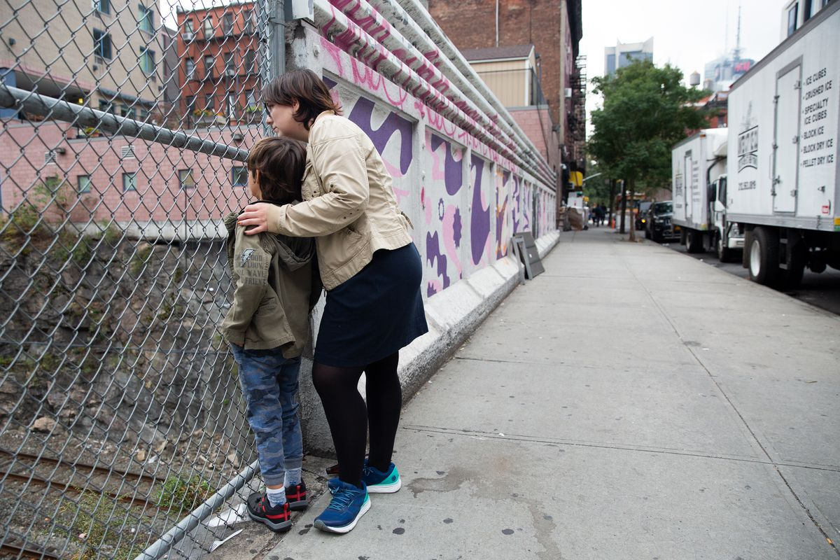 Eliyanna Kaiser and her seven-year-old son, who has autism, watch for Amtrak trains near their Hell's Kitchen home, Oct. 14, 2019.