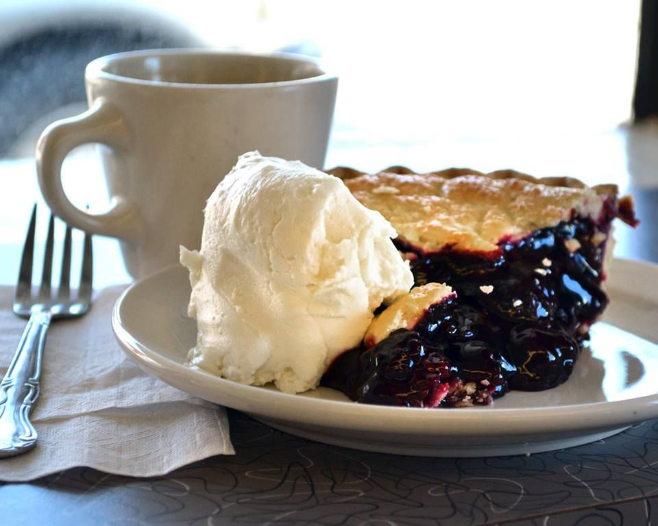 A slice of blueberry or blackberry pie with a big scoop of ice cream on a small plate besides a coffee mug and place setting on a sunny countertop