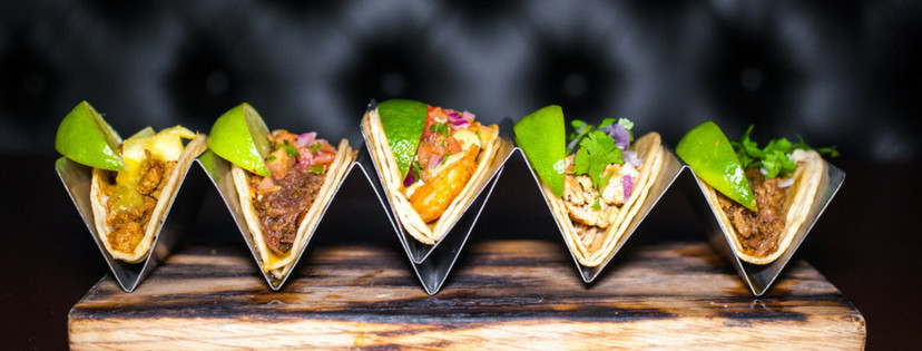 Tacos arranged vertically on a metal tray.