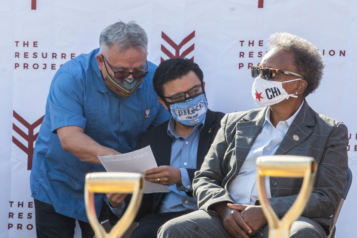 Chicago Mayor Lori Lightfoot sits onstage as Raul Raymundo, Resurrection Project CEO (left), talks to Ald. Byron Sigcho-Lopez (25th) on Thursday at the groundbreaking ceremony for Casa Durango, a Resurrection Project affordable housing development in the Pilsen neighborhood.