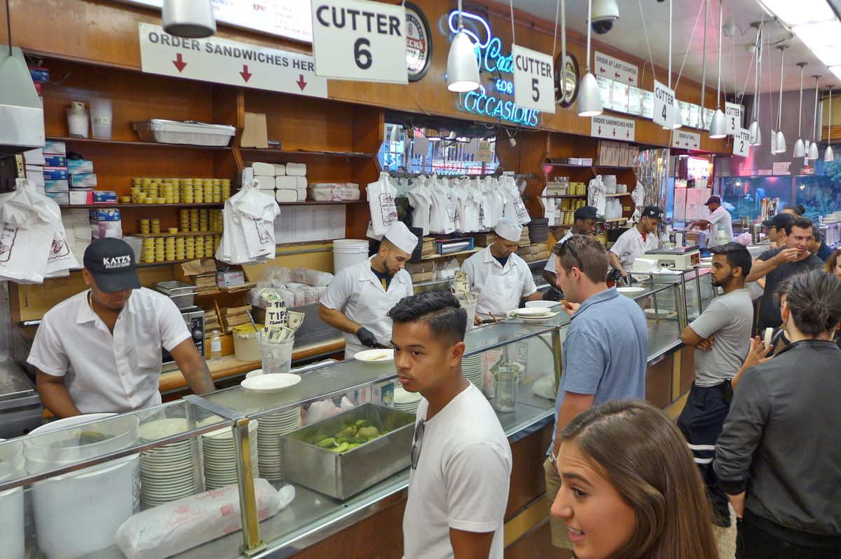 A throng of customers in front of a counter where carvers cut meat with long knives...