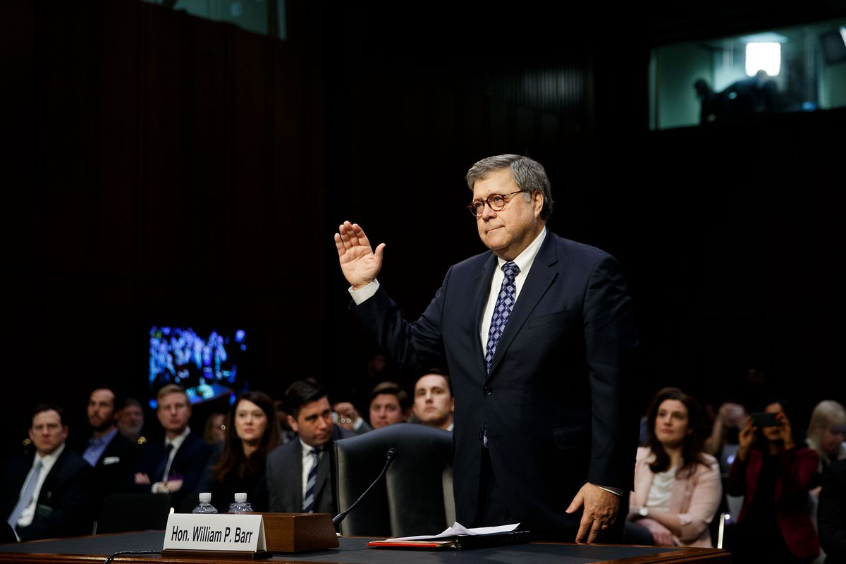 Barr raises his right hand behind a desk.