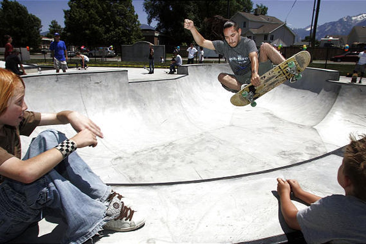 Eleven-year-olds Hayden Seager, left, and Chris Howard watch as Shane Padilla of West Valley City glides through the air at a new skate park on a warm and sunny Wednesday. The park is in Midvale.