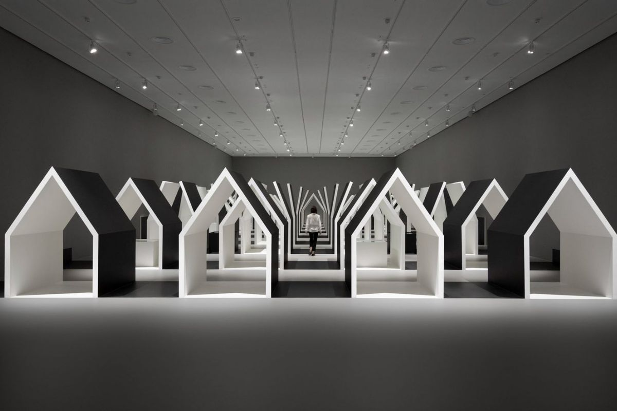 Woman walking through gallery with small houses