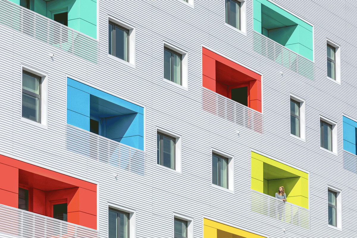 A mix of windows and recessed balconies. There is red, blue, green, and yellow against a silvery, white exterior.