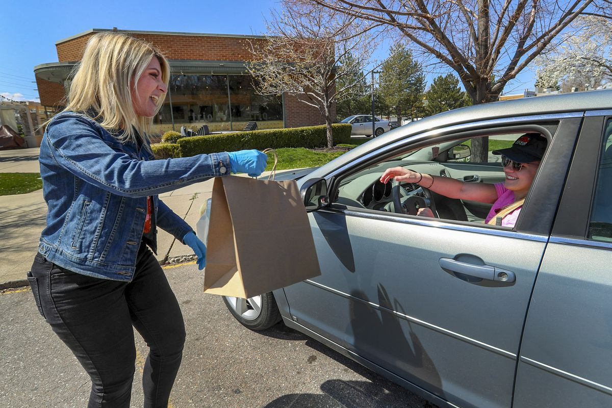 Ashlee Francom, general manager at Cafe Trio in Salt Lake City, shares a laugh with Megan Stanley as she delivers afamily meal to the furloughed employee outside of the restaurant on Wednesday, April 1, 2020. Cafe Trio was forced to furlough most of its employees due to COVID-19 restrictions. The restaurant is providing a free daily meal to all of its employees, including those who have been laid off. The employees pick up their meal, which changes daily, between 1 p.m. and 3 p.m.