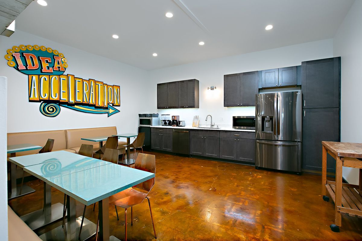 A kitchen with a stainless steel fridge and brown cabinets faces a booth-like seating area.