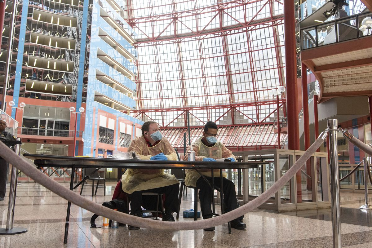 Two attendants wait to check workers' and visitors' temperatures before they can enter the Thompson Center on Monday.