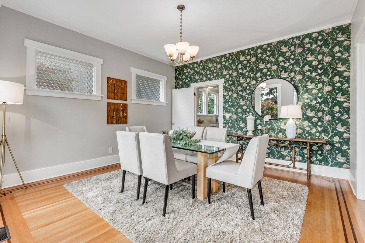A dining room has seating for six, a gray rug, and a green and white floral accent wall.