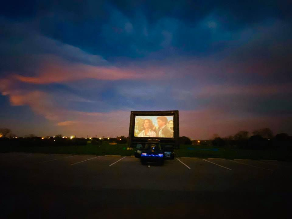 A movie places at an outdoor movie screen during dusk in a parking lot