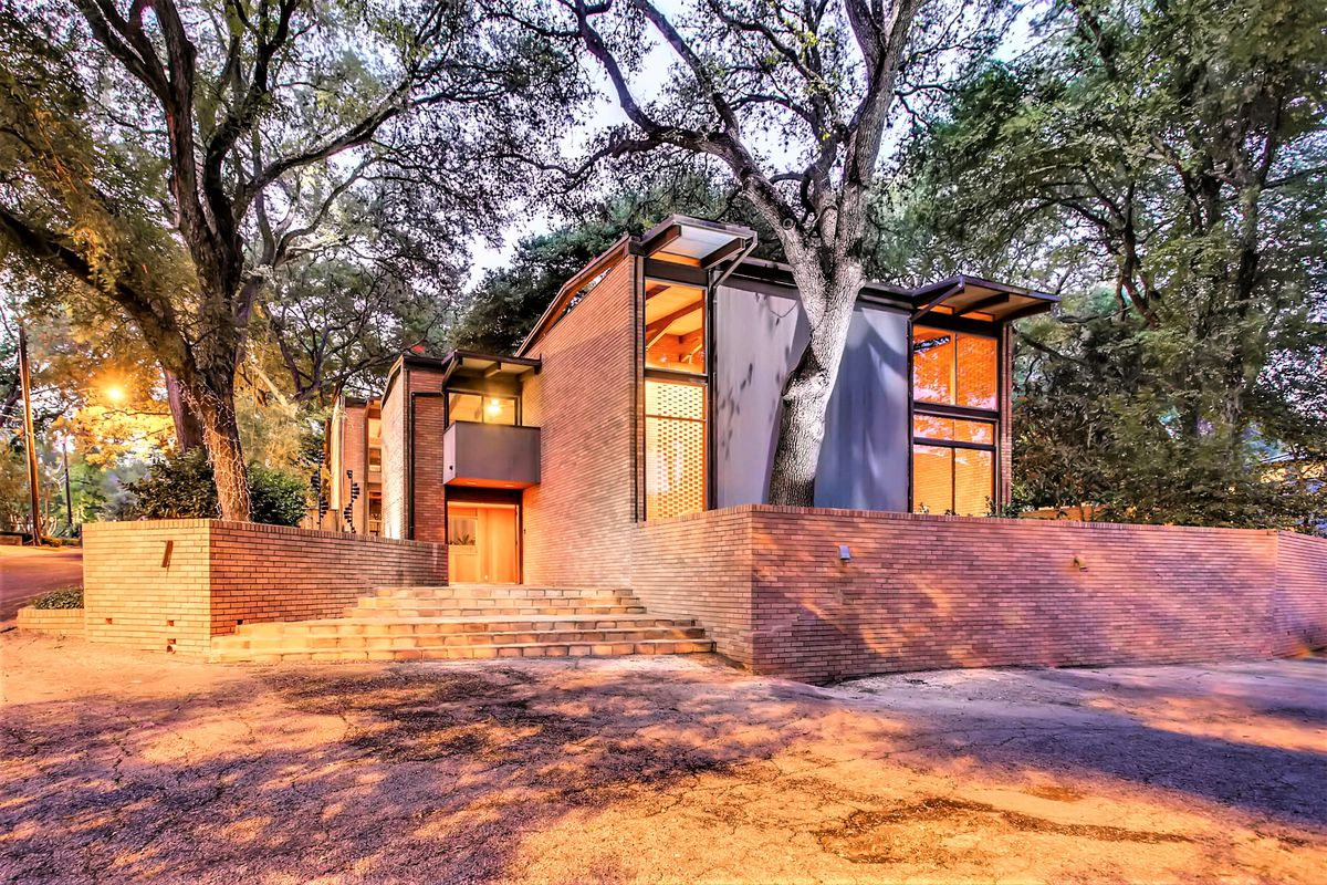 Two-story brick 1964 modern home with large, two-story windows, trees in front