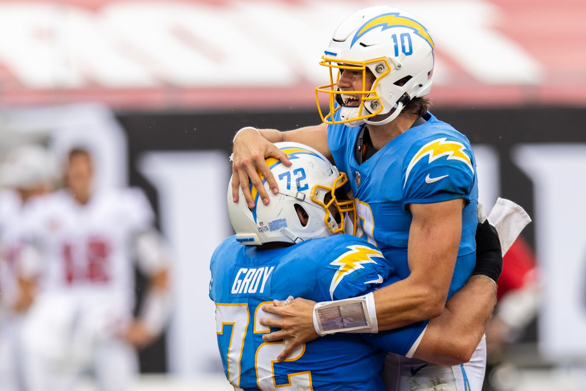 Justin Herbert #10 of the Los Angeles Chargers celebrates with teammate Ryan Groy #72 after throwing a touchdown during the third quarter of a game against the Tampa Bay Buccaneers at Raymond James Stadium on October 04, 2020 in Tampa, Florida.
