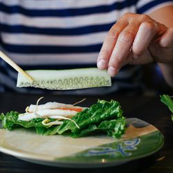 Once the fish is served, wet a rice paper with the provided warm water, stack high with veggies, and pile on the catfish.