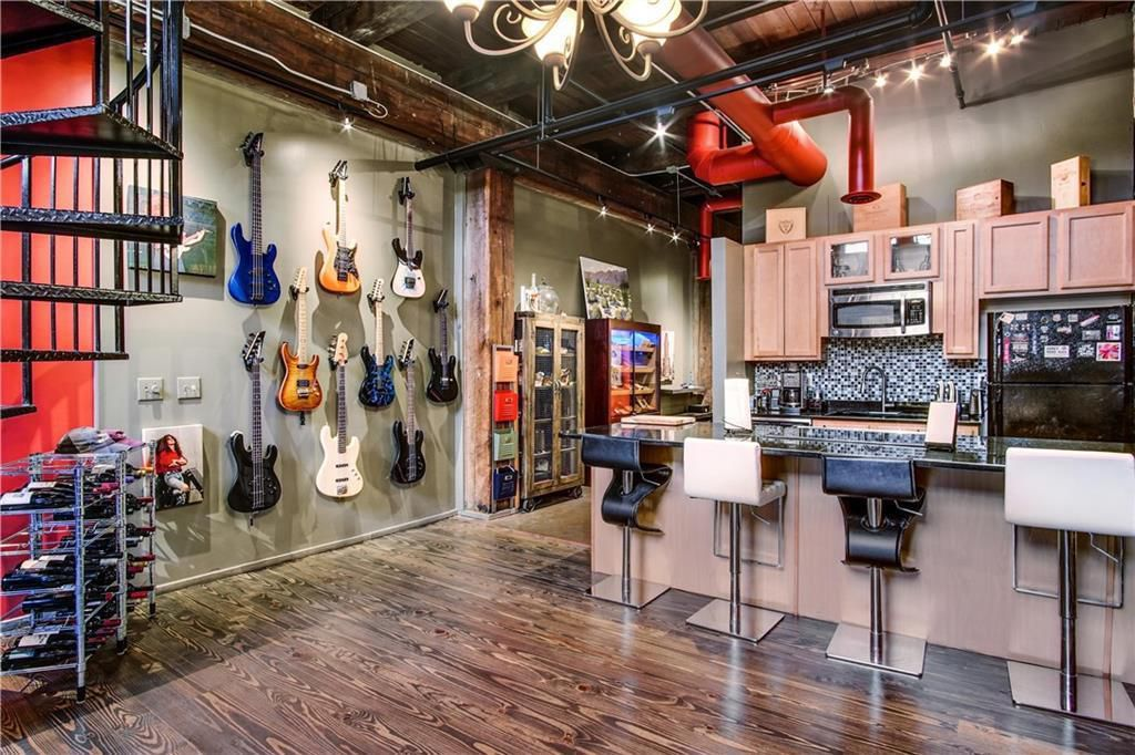 A guitar wall beside a kitchen with light cabinetry in a big loft space.