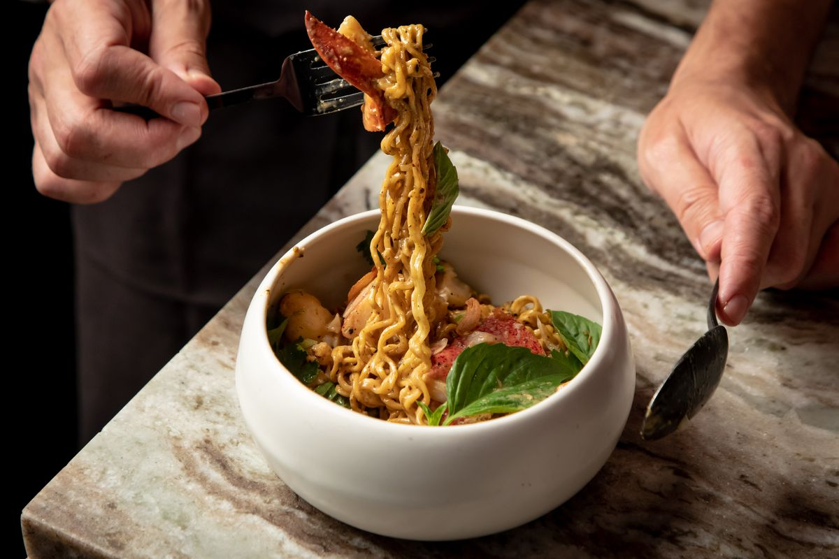 Lobster noodles at Wayan get pulled up from a white bowl.