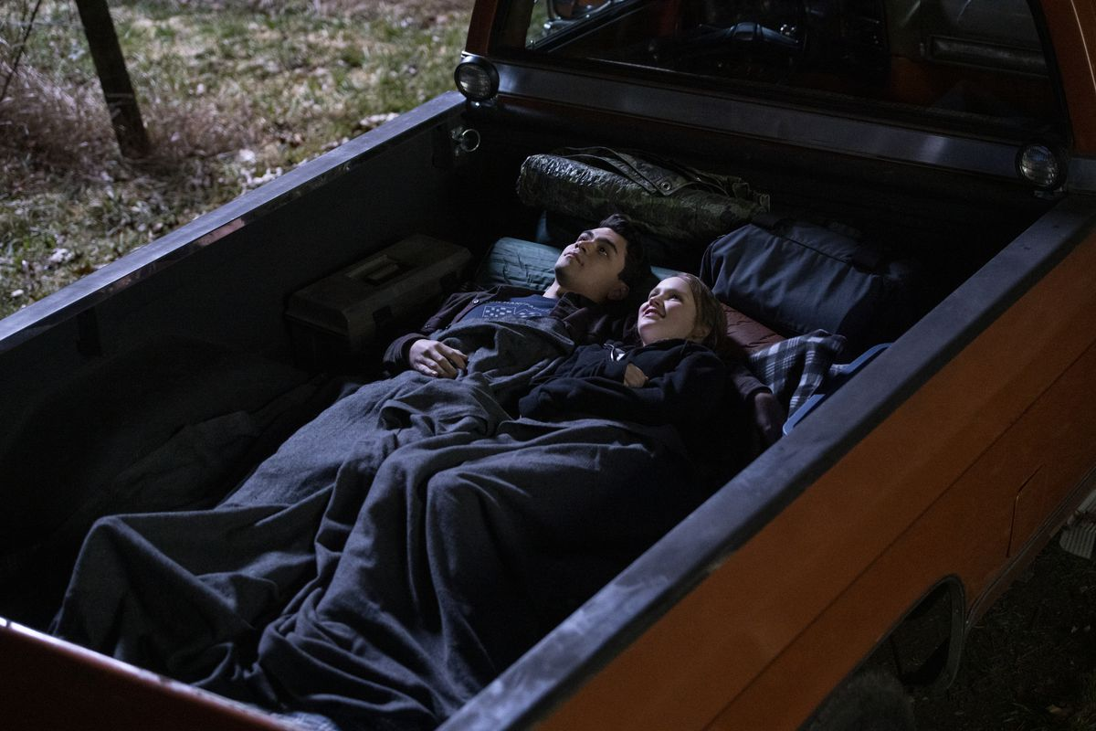 Adam Irigoyen and Talitha Eliana Bateman lie under a blanket in a truck bed and look up at the night sky in Netflix's series Away.