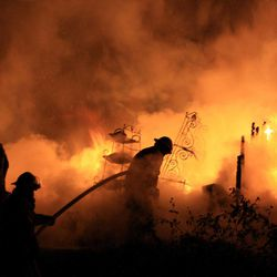 Unionville firefighters are silhouetted against flames billowing from a Kingdom Road home late Sunday night, Sept. 23, 2012, near Rover, Tenn. Four people died in the fire, authorities said.