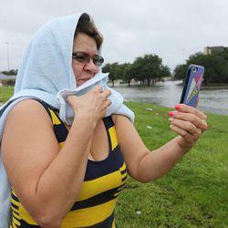 Maria GutiÉrrez takes a photo during Tropical Storm Harvey in Houston on Tuesday, Aug. 29, 2017.
