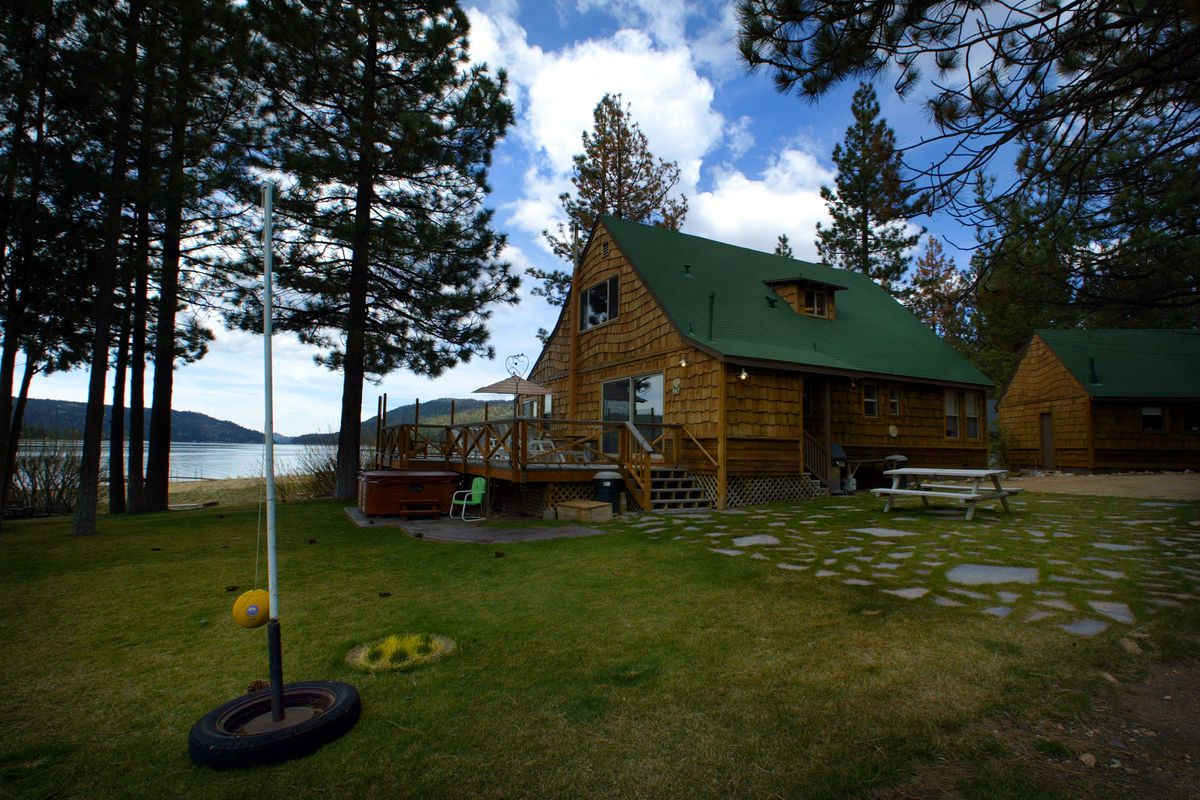 A cabin nestled among tall pine trees with a view of Big Bear Lake is a perfect vacation spot in Fan