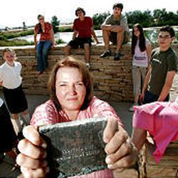 Margaret Wahlstrom, holding a piece of the World Trade Center, stands with members of Youth of Promise at the Kaysville site of Utah Unites in Hope memorial. Wahlstrom's husband lost his mother and sister in the attack.