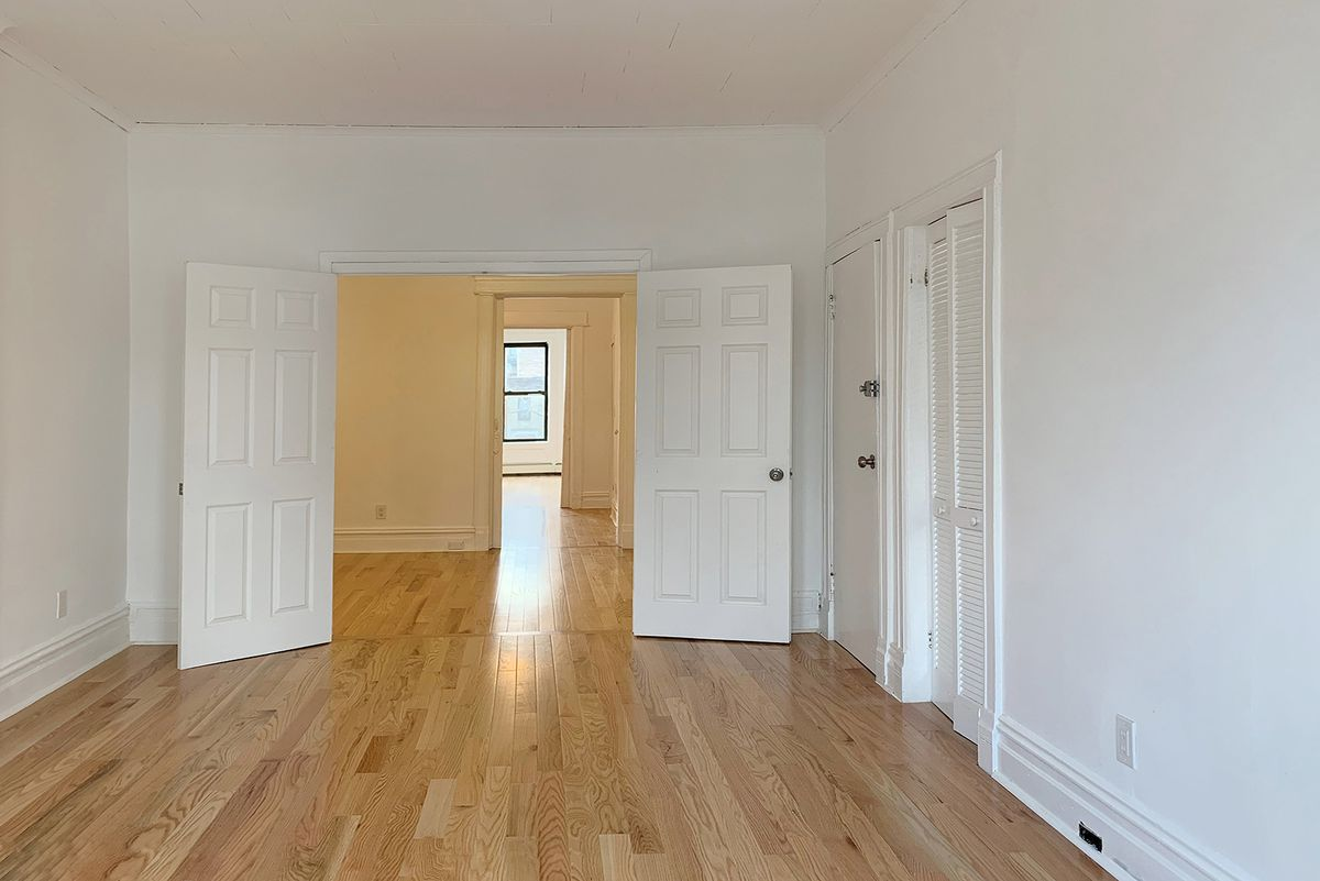 A living area with hardwood floors and white walls.