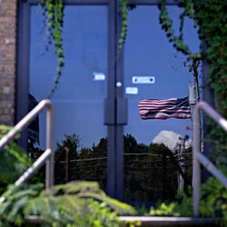 """In this Aug. 22, 2012 photo, an American flag is reflected in the entrance of a closed carpet store along the Interstate 75 corridor of carpet businesses in Dalton, Ga. Collapsing industry or not, Dalton city officials are still the proud owners of the label """"Carpet Capital of the World,"""" but what they aren't happy about is the most recent label: The city that is leading the nation in the number of job losses per capita this year. The city that makes nearly 75 percent of the nation's flooring has lost 4,600 jobs between June 2011 and June 2012 according to the United States Bureau of Labor Statistics. Dalton's economy hit bottom in 2009 with the collapse of the housing market, taking hundreds of distributor business and support services down with it and struggling to recover in recent years."""