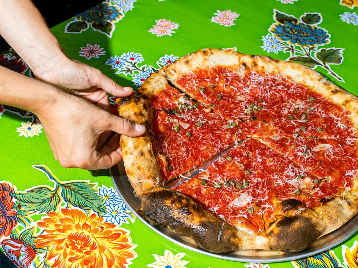 A full pizza pie at Blotto covered in tomato sauce against a bright green flowered placemat