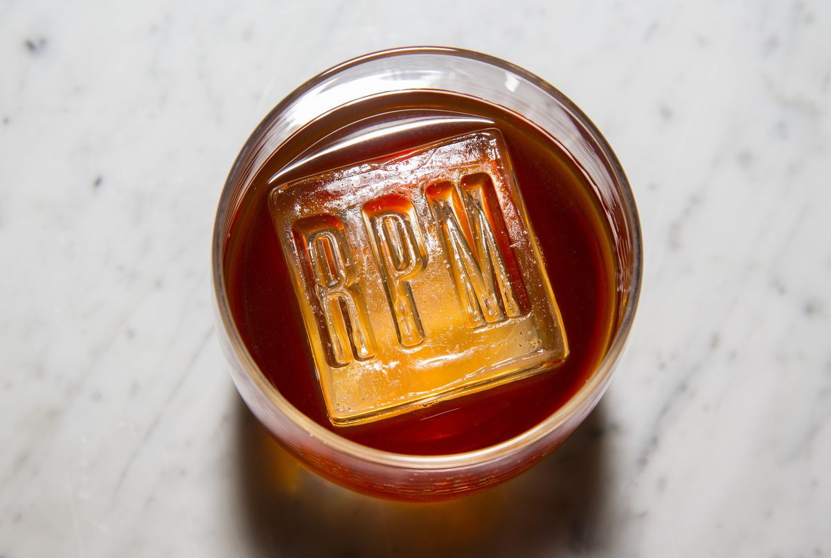A whisky drink in a highball glass with a single block ice cube.