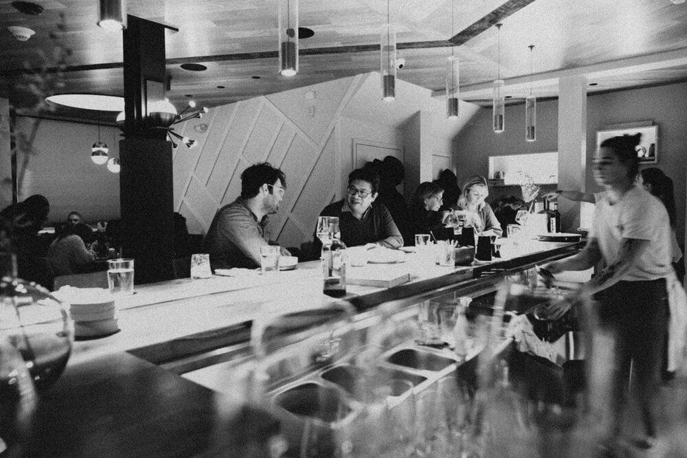 Black and white view of the inside of a cocktail bar, with some smiling patrons visible.