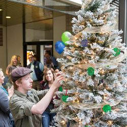 Braydin Burr, 16, of Ogden, whose mother received a liver transplant in 2007, hangs a Christmas tree ornament at a ceremony hosted by Intermountain Donor Services in Salt Lake City on Wednesday, Dec. 21, 2016.