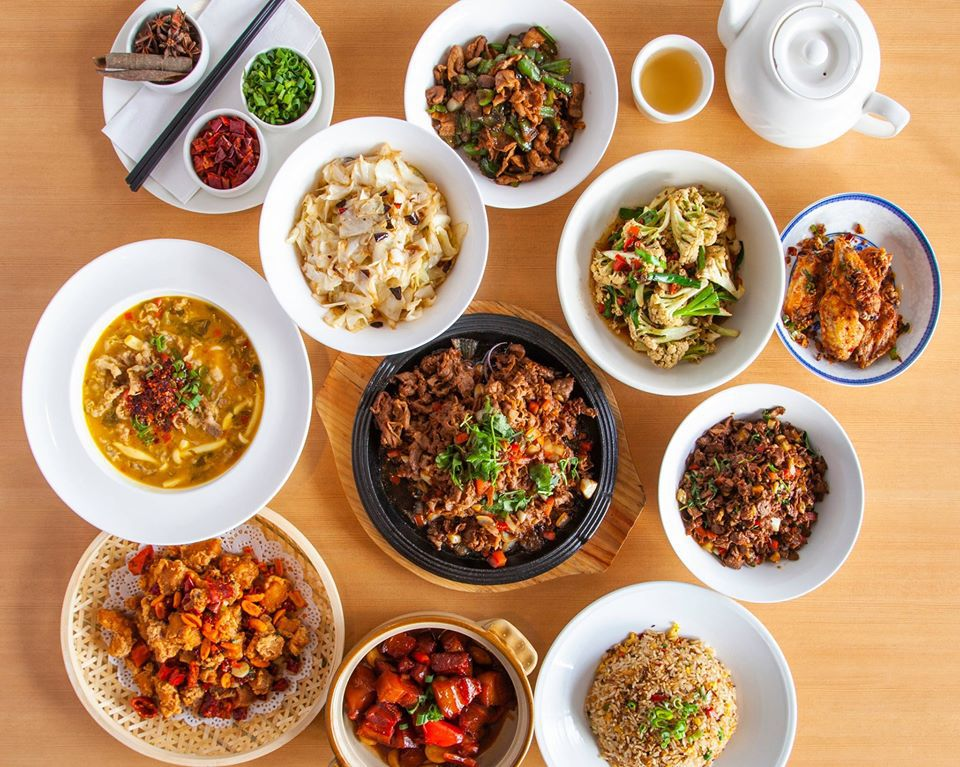 Overhead view of a table full of Chinese food and a pot of tea