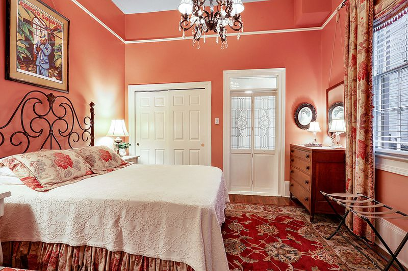 Bedroom with peach walls, wood floors and cut glass doors