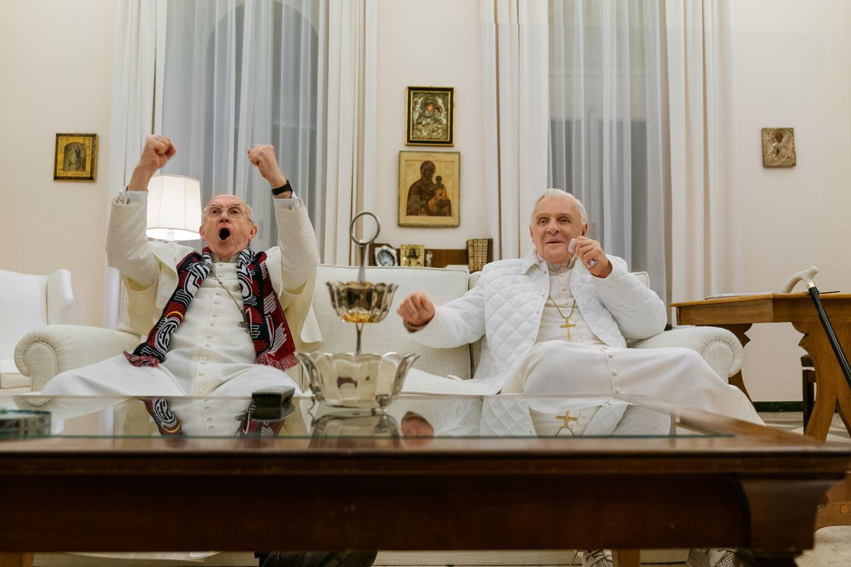 Jonathan Pryce and Anthony Hopkins, both dressed in papal white robes, sit on a couch together in a white room full of religious iconography, cheering on a sporting event on TV.