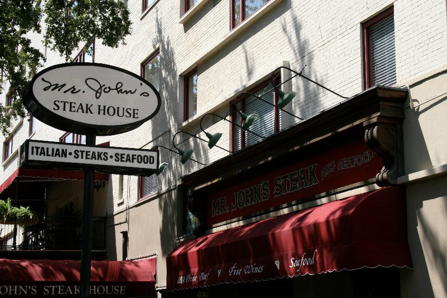 Exterior of restaurant on St. Charles Avenue with red awning and white and black Mr. John's Steakhouse sign