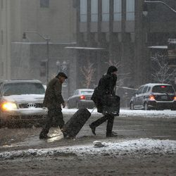 Pedestrians brave the icy and snowy streets in Salt Lake City on Thursday, Dec. 19, 2013.