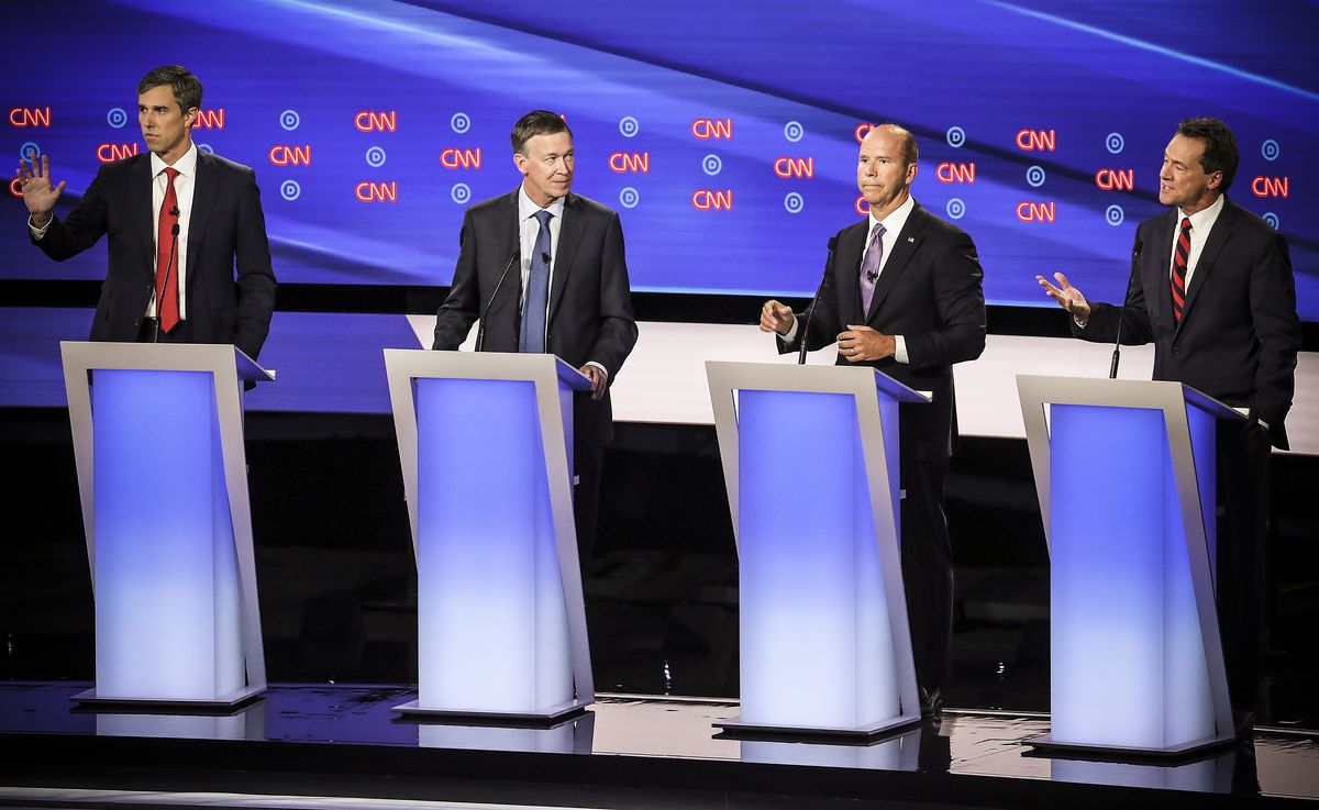 Democratic presidential candidate Montana Gov. Steve Bullock (right) speaks while former Maryland congressman John Delaney, former Colorado governor John Hickenlooper, and former Texas congressman Beto O'Rourke listen during the Democratic Presidential De