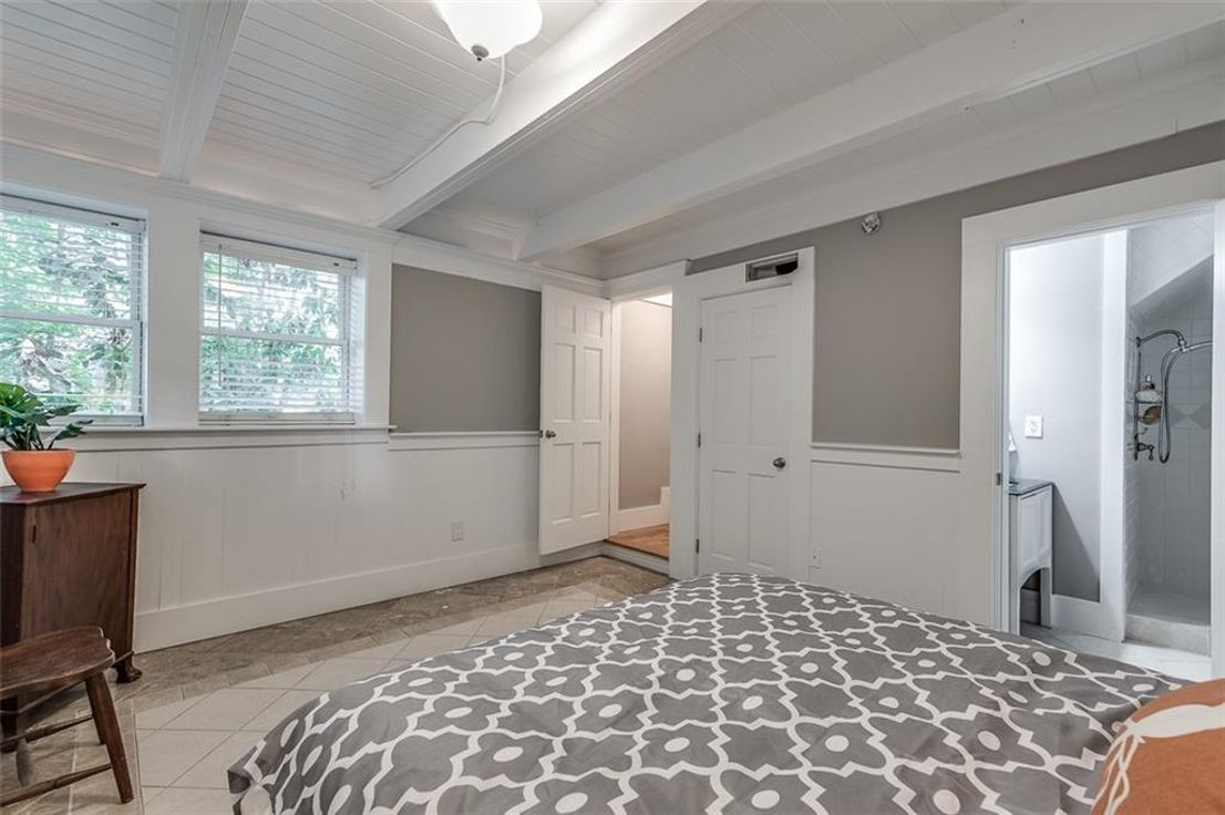 A finished basement with gray walls and a large bed with a gray patterned comforter.