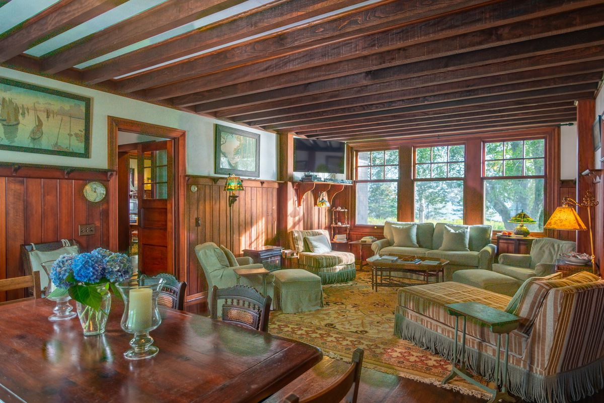 A living room has exposed beams, rugs, a dining table, and large windows on one side.