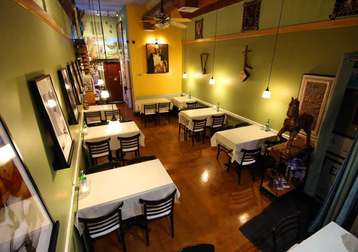 A long, narrow restaurant features tables with white tablecloths, dim lighting, and pale green walls.