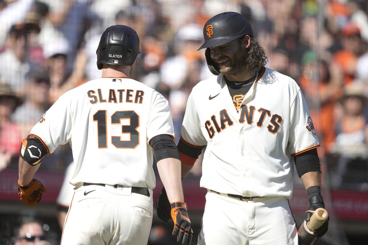 Austin Slater #13 of the San Francisco Giants is congratulated by Brandon Crawford #35 after Slater hit a pinch-hit solo home run against the San Diego Padres in the bottom of the sixth inning at Oracle Park on October 02, 2021 in San Francisco, California.